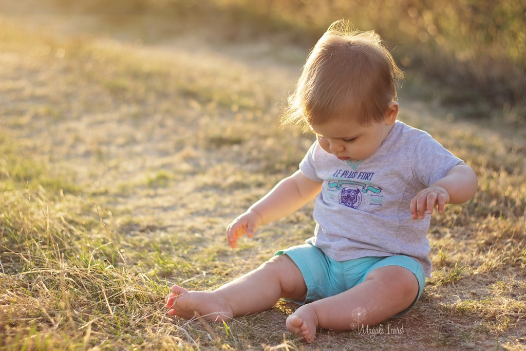 Seance photos d'un bébé de 6 mois assis dans l'herbe dans l'ardeche